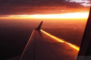 aircraft wing lit by sunrise embraer 195 sp-lnn.JPG